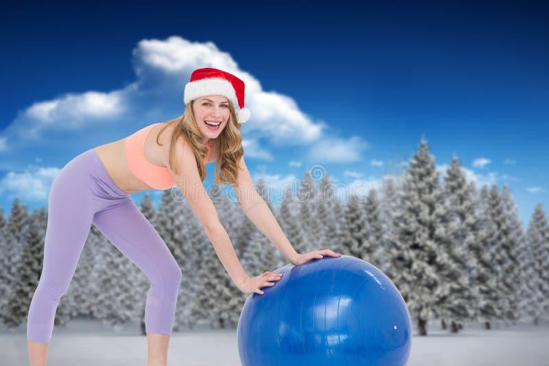 Σύνθετη εικόνα της εορταστικής ξανθής γυναίκας που χρησιμοποιεί τη σφαίρα άσκησης στοκ φωτογραφίες