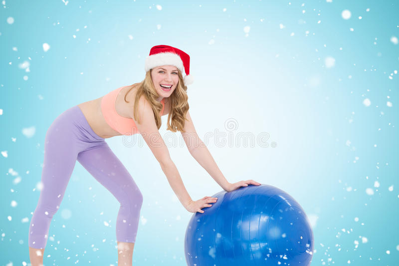 Σύνθετη εικόνα της εορταστικής ξανθής γυναίκας που χρησιμοποιεί τη σφαίρα άσκησης στοκ φωτογραφίες με δικαίωμα ελεύθερης χρήσης