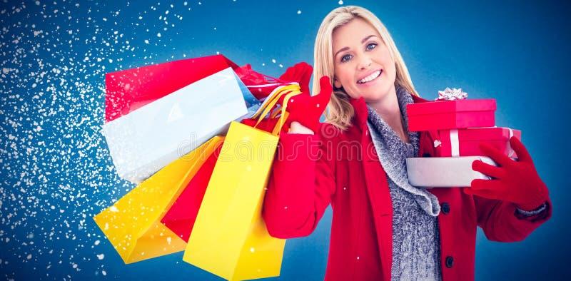 Σύνθετη εικόνα της εορταστικής ξανθής εκμετάλλευσης πολλά δώρα στοκ φωτογραφία με δικαίωμα ελεύθερης χρήσης