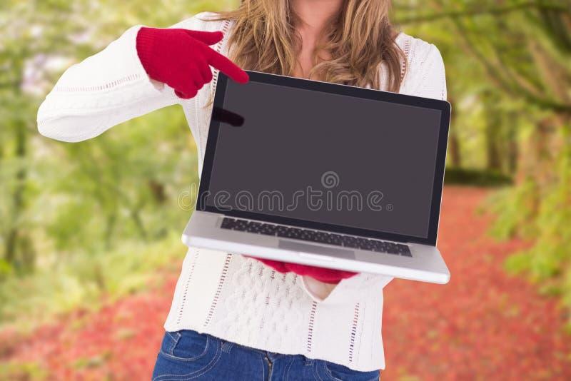 Σύνθετη εικόνα της εορταστικής ξανθής υπόδειξης το lap-top στοκ εικόνες με δικαίωμα ελεύθερης χρήσης