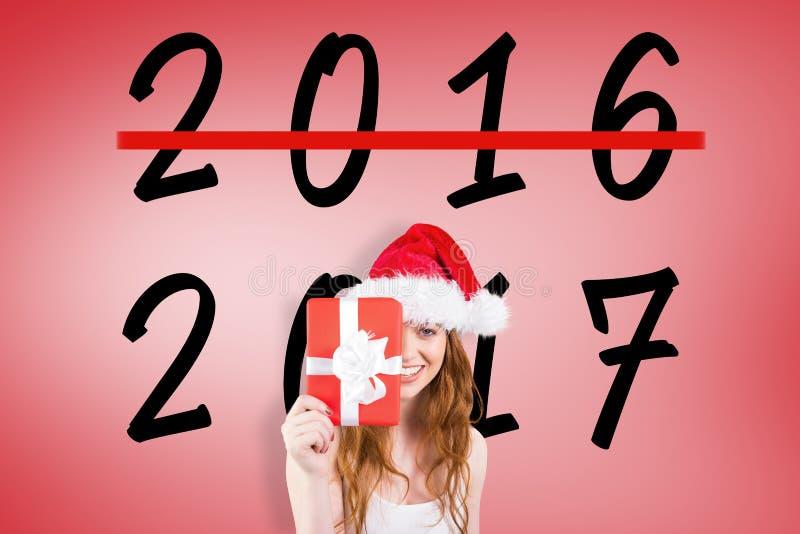 Σύνθετη εικόνα της εορταστικής redhead εκμετάλλευσης ένα δώρο στοκ εικόνες με δικαίωμα ελεύθερης χρήσης