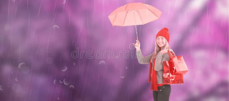 Σύνθετη εικόνα της εορταστικών ξανθών ομπρέλας και των τσαντών εκμετάλλευσης στοκ εικόνες