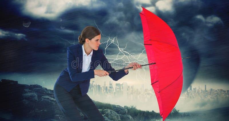 Σύνθετη εικόνα της επιχειρηματία που κρατά την κόκκινη ομπρέλα στοκ εικόνα