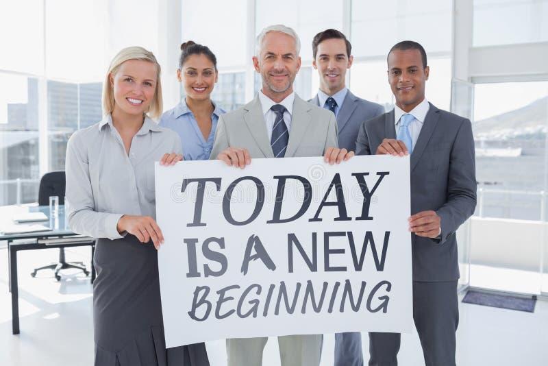 Σύνθετη εικόνα της επιχειρησιακής ομάδας που κρατά τη μεγάλη κενή αφίσα στοκ φωτογραφία