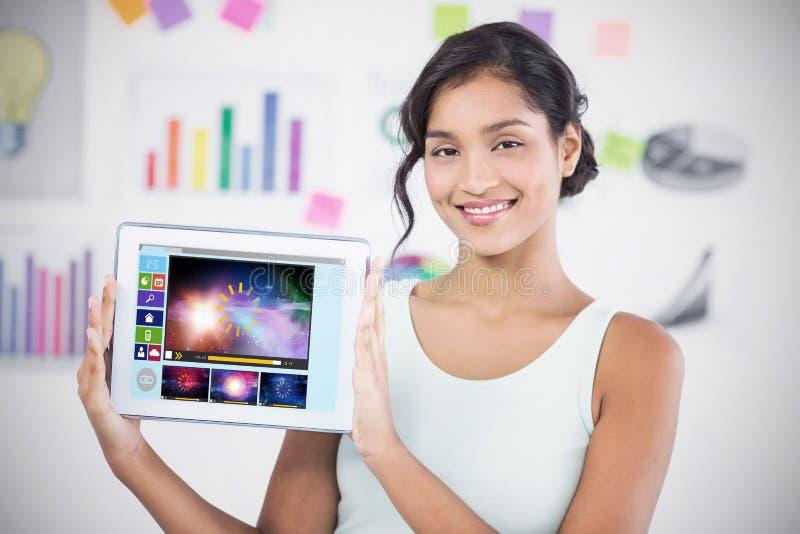 Σύνθετη εικόνα της ευτυχούς επιχειρηματία που παρουσιάζει ψηφιακή ταμπλέτα στο δημιουργικό γραφείο στοκ εικόνες