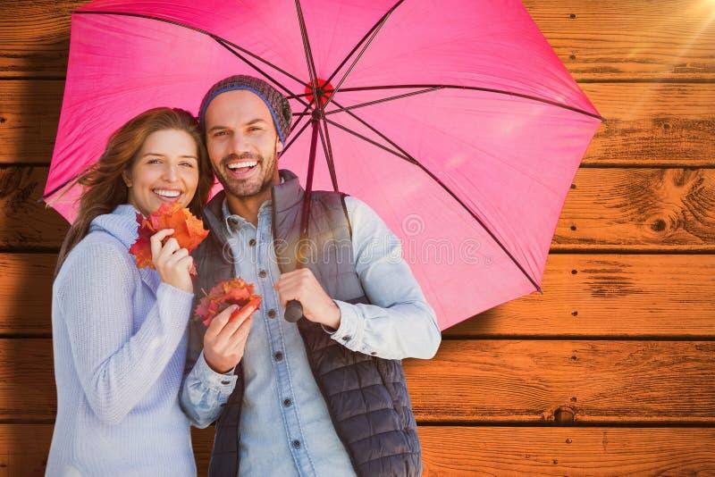 Σύνθετη εικόνα της ευτυχούς νέας ομπρέλας εκμετάλλευσης ζευγών στοκ εικόνες