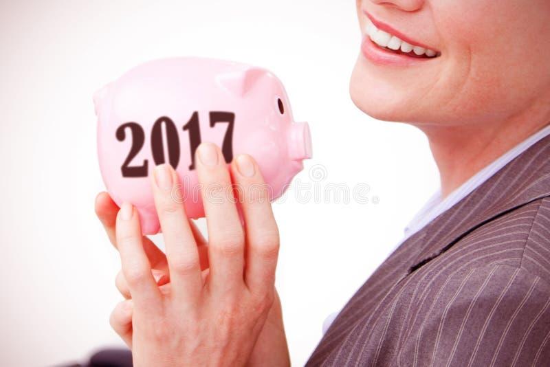 Σύνθετη εικόνα της εύθυμης επιχειρηματία που κρατά ένα piggybank στοκ εικόνες