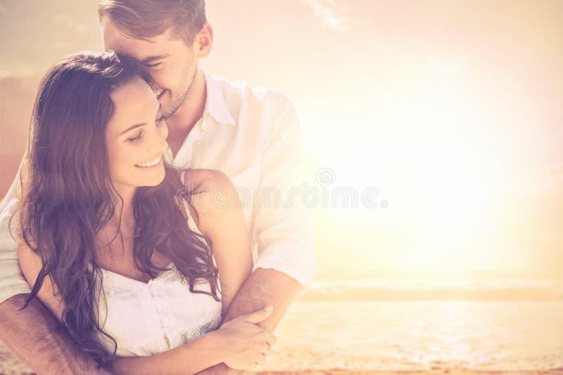 Σύνθετη εικόνα της ελκυστικής αγκαλιάς ζευγών στοκ φωτογραφίες