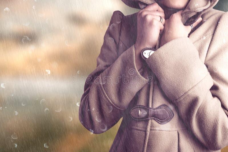 Σύνθετη εικόνα της ελκυστικής γυναίκας που φορά ένα θερμό παλτό με την κουκούλα που αυξάνεται στοκ φωτογραφίες με δικαίωμα ελεύθερης χρήσης