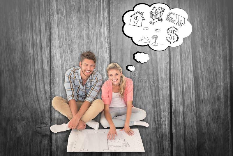 Σύνθετη εικόνα της ελκυστικής νέας συνεδρίασης ζευγών που εξετάζει το σχεδιάγραμμα στοκ εικόνα με δικαίωμα ελεύθερης χρήσης