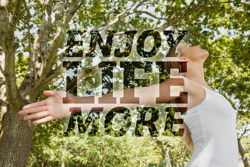 Σύνθετη εικόνα της ικανοποιημένης νέας γυναίκας που κάνει τη γιόγκα σε ένα πάρκο στοκ εικόνα με δικαίωμα ελεύθερης χρήσης