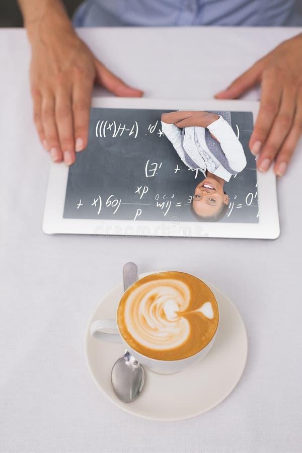 Σύνθετη εικόνα της κινηματογράφησης σε πρώτο πλάνο της ψηφιακών ταμπλέτας και του καφέ στον πίνακα στοκ φωτογραφίες με δικαίωμα ελεύθερης χρήσης