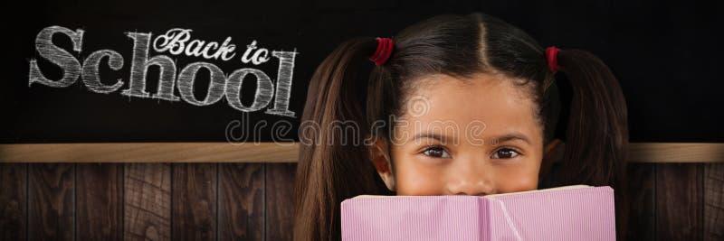 Σύνθετη εικόνα της μαθήτριας που καλύπτει το στόμα με το βιβλίο στοκ φωτογραφία