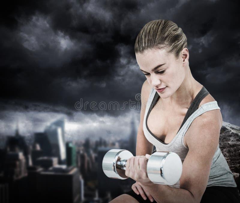 Σύνθετη εικόνα της μυϊκής επίλυσης γυναικών με τους αλτήρες στοκ φωτογραφία
