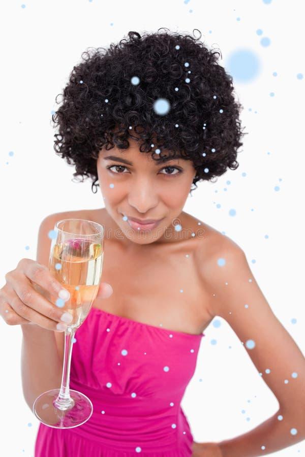 Σύνθετη εικόνα της νέας γυναίκας που κρατά ένα ποτήρι της σαμπάνιας εξετάζοντας τη κάμερα στοκ εικόνα
