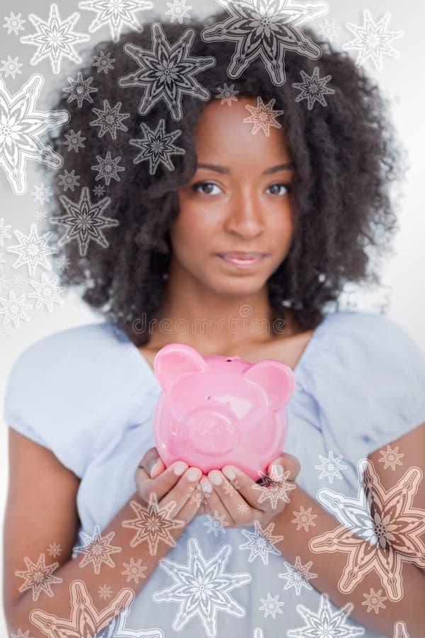 Σύνθετη εικόνα της νέας γυναίκας που κρατά μια ρόδινη piggy τράπεζα κοντά στοκ φωτογραφία με δικαίωμα ελεύθερης χρήσης