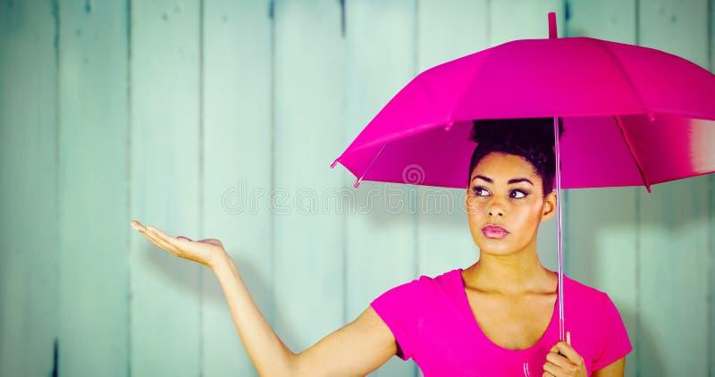 Σύνθετη εικόνα της νέας γυναίκας που φέρνει τη ρόδινη ομπρέλα στοκ εικόνες με δικαίωμα ελεύθερης χρήσης