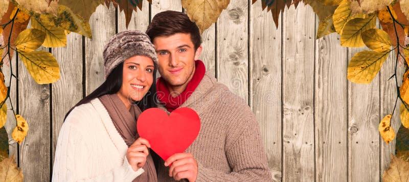 Σύνθετη εικόνα της νέας κόκκινης καρδιάς εκμετάλλευσης χαμόγελου ζευγών στοκ φωτογραφίες