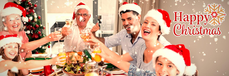 Σύνθετη εικόνα της οικογένειας στα καπέλα santas που ψήνουν τα γυαλιά κρασιού να δειπνήσει στον πίνακα στοκ φωτογραφίες με δικαίωμα ελεύθερης χρήσης