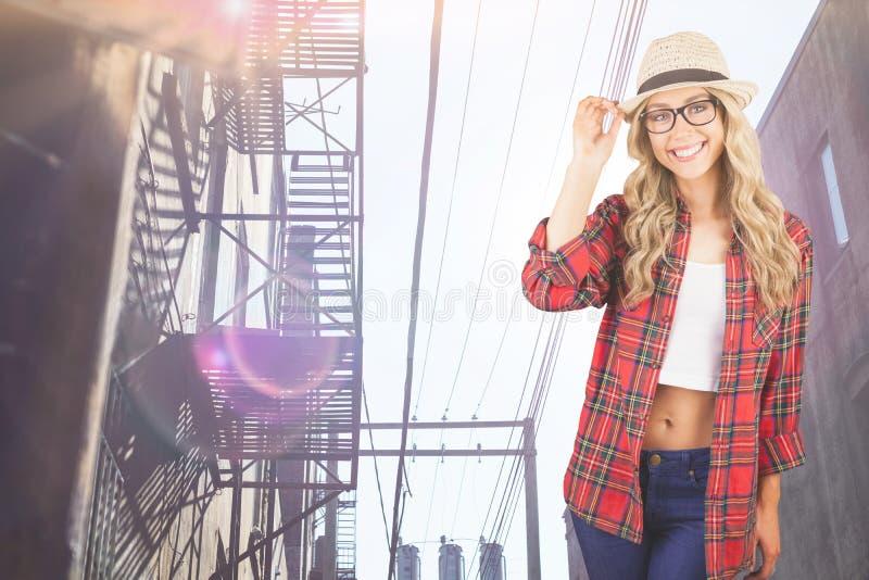 Σύνθετη εικόνα της πανέμορφης τοποθέτησης hipster χαμόγελου ξανθής στοκ εικόνα