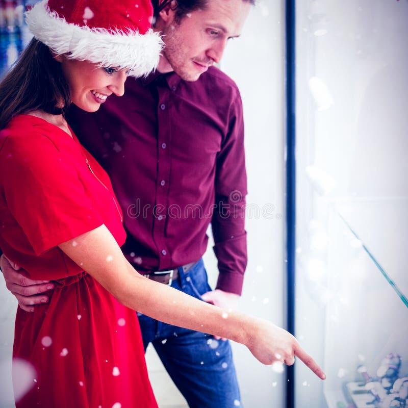 Σύνθετη εικόνα της πλάγιας όψης του ζεύγους στην ενδυμασία Χριστουγέννων που εξετάζει την επίδειξη wristwatch στοκ εικόνα με δικαίωμα ελεύθερης χρήσης
