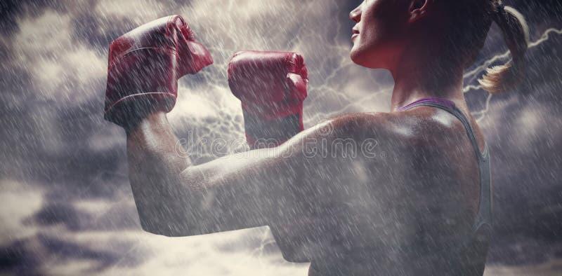 Σύνθετη εικόνα της πλάγιας όψης του θηλυκού μπόξερ με την πάλη της θέσης στοκ φωτογραφίες