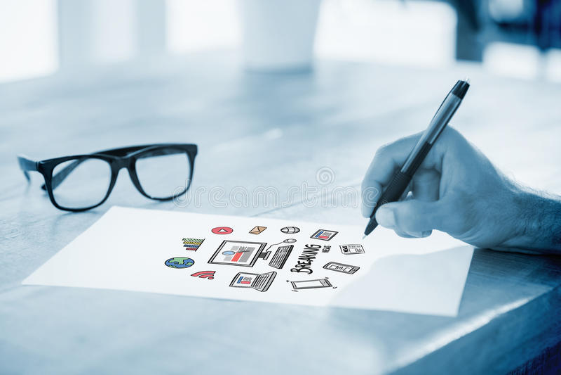 Σύνθετη εικόνα της πλάγιας όψης του χεριού που γράφει στην άσπρη σελίδα στο λειτουργώντας γραφείο στοκ φωτογραφίες με δικαίωμα ελεύθερης χρήσης
