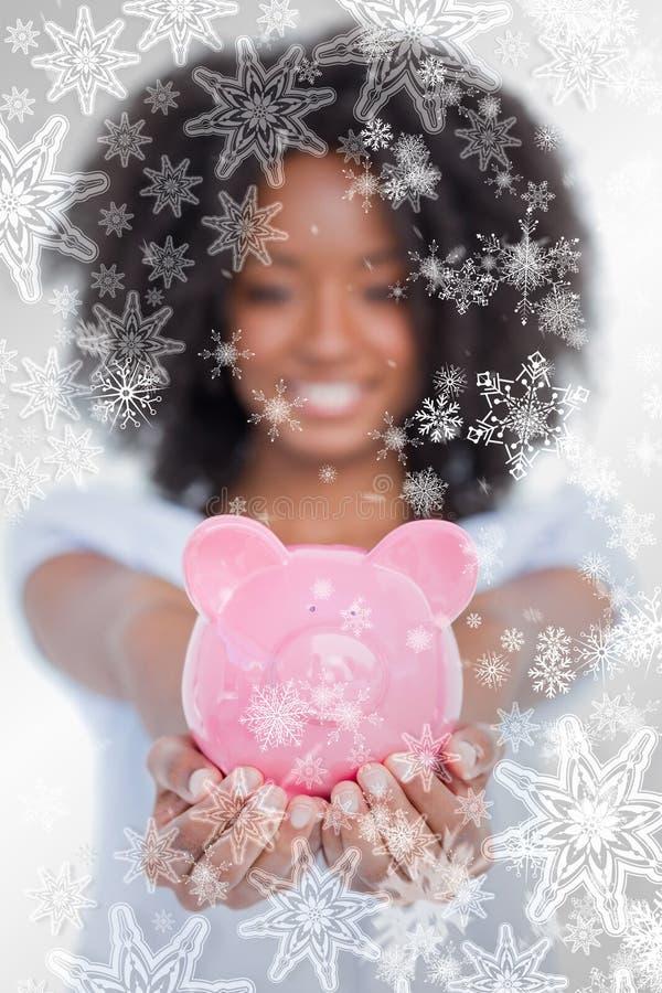 Σύνθετη εικόνα της ρόδινης piggy τράπεζας που κατέχει μια γυναίκα μπροστά από τη κάμερα στοκ εικόνα με δικαίωμα ελεύθερης χρήσης