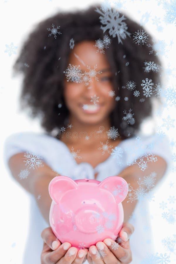 Σύνθετη εικόνα της ρόδινης piggy τράπεζας που κατέχει μια νέα χαμογελώντας γυναίκα με τη σγουρή τρίχα στοκ εικόνα με δικαίωμα ελεύθερης χρήσης