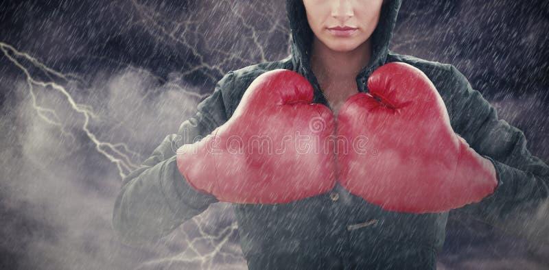 Σύνθετη εικόνα της σοβαρής νέας γυναίκας στα κόκκινα εγκιβωτίζοντας γάντια και τη μαύρη κουκούλα στοκ εικόνες