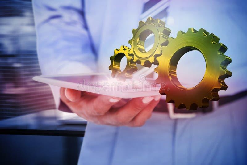 Σύνθετη εικόνα της στενής επάνω άποψης του επιχειρηματία που χρησιμοποιεί τον υπολογιστή ταμπλετών στοκ εικόνες