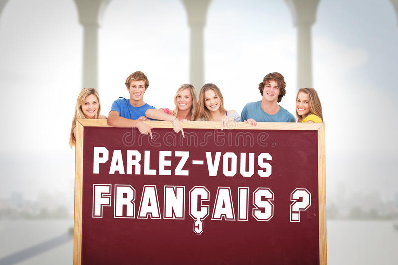 Σύνθετη εικόνα της χαμογελώντας ομάδας ανθρώπων με ένα κενό διάστημα όπως δείχνουν την στοκ φωτογραφία με δικαίωμα ελεύθερης χρήσης
