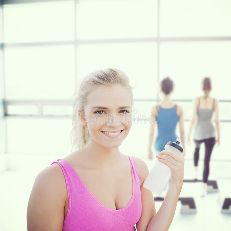 Σύνθετη εικόνα της χαμογελώντας υγιούς γυναίκας με το μπουκάλι νερό στοκ εικόνες
