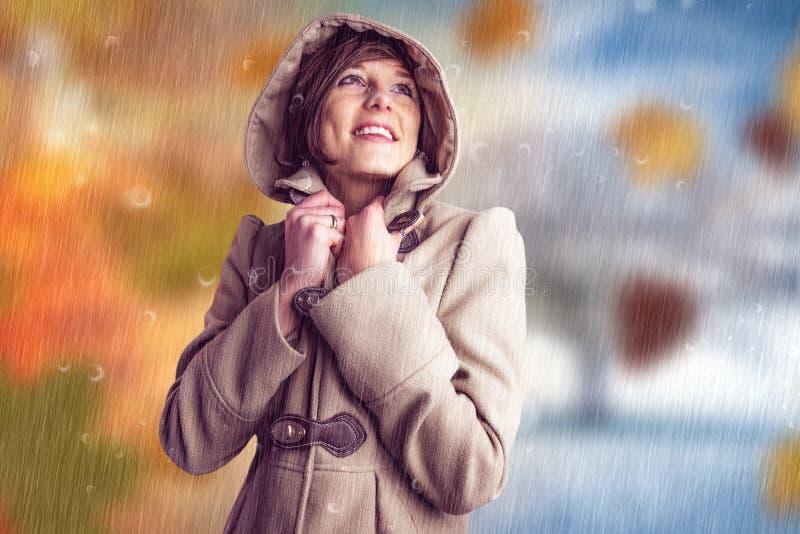 Σύνθετη εικόνα της χαμογελώντας όμορφης γυναίκας στο χειμερινό παλτό που ανατρέχει στοκ φωτογραφίες