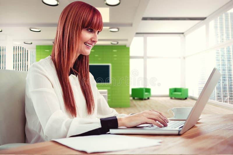 Σύνθετη εικόνα της χαμογελώντας hipster επιχειρηματία που χρησιμοποιεί το lap-top της στοκ εικόνες