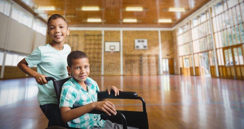 Σύνθετη εικόνα της ωθώντας αναπηρικής καρέκλας φίλων αγοριών στοκ φωτογραφίες