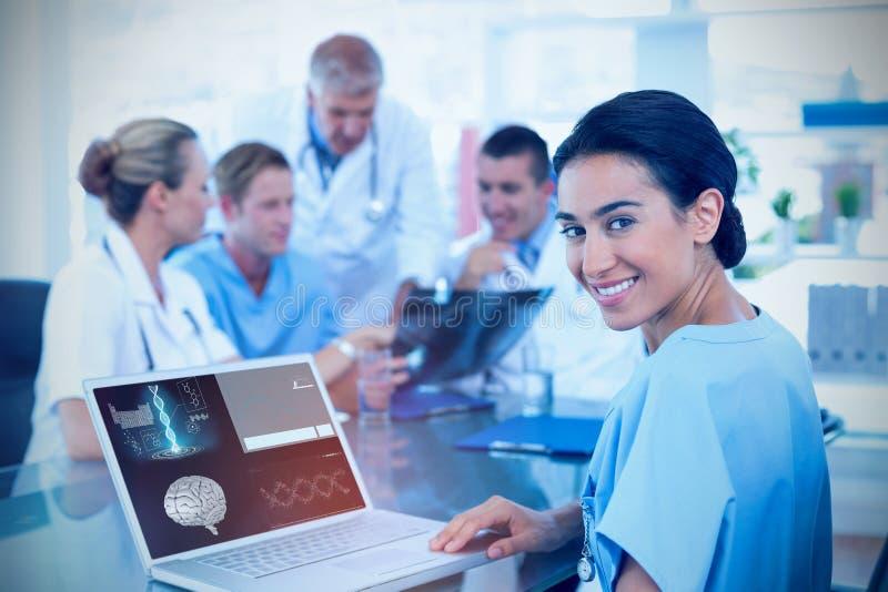 Σύνθετη εικόνα της όμορφης δακτυλογράφησης γιατρών χαμόγελου στο πληκτρολόγιο με την ομάδα της πίσω στοκ εικόνες