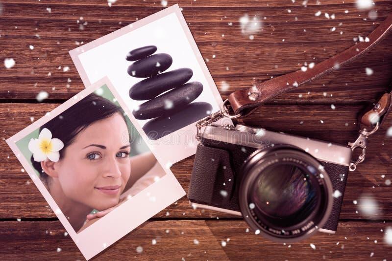 Σύνθετη εικόνα της όμορφης χαλάρωσης brunette στον πίνακα μασάζ που χαμογελά στη κάμερα στοκ φωτογραφία με δικαίωμα ελεύθερης χρήσης