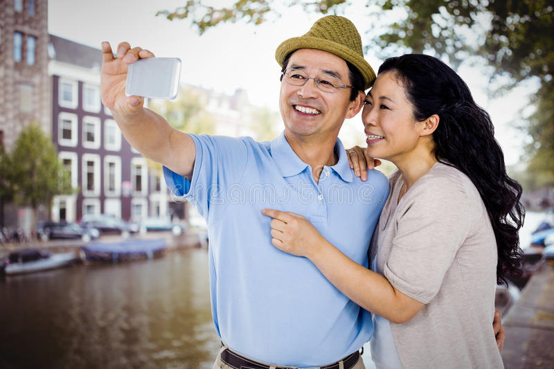 Σύνθετη εικόνα του άνδρα και της γυναίκας που παίρνουν μια εικόνα στοκ εικόνα με δικαίωμα ελεύθερης χρήσης