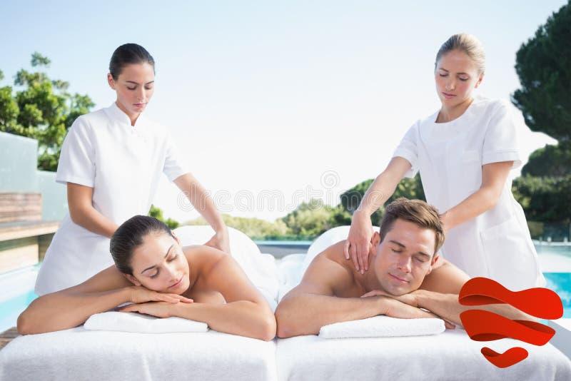Σύνθετη εικόνα του ήρεμου ζεύγους που απολαμβάνει το poolside μασάζ ζευγών στοκ εικόνα με δικαίωμα ελεύθερης χρήσης