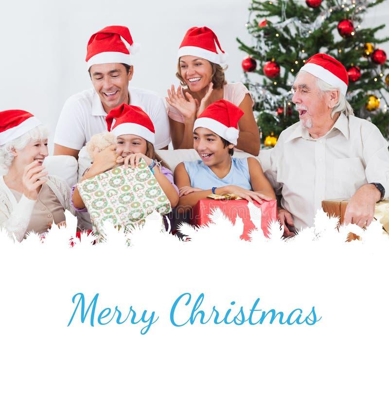 Σύνθετη εικόνα του ανοίγοντας χριστουγεννιάτικου δώρου μικρών κοριτσιών στοκ εικόνες