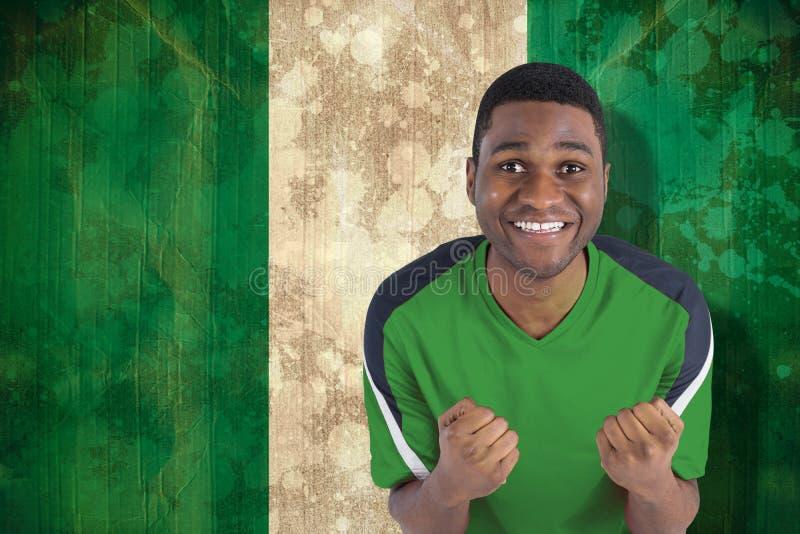 Σύνθετη εικόνα του ενθαρρυντικού οπαδού ποδοσφαίρου στο πράσινο Τζέρσεϋ στοκ φωτογραφίες