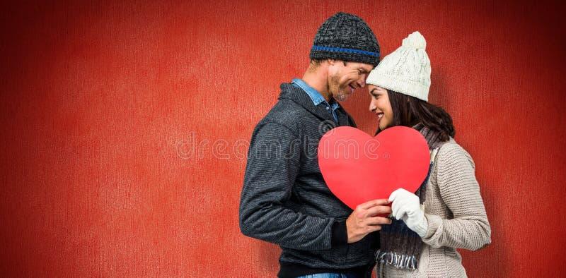 Σύνθετη εικόνα του εορταστικού ζεύγους στα χειμερινά ενδύματα στοκ εικόνες με δικαίωμα ελεύθερης χρήσης