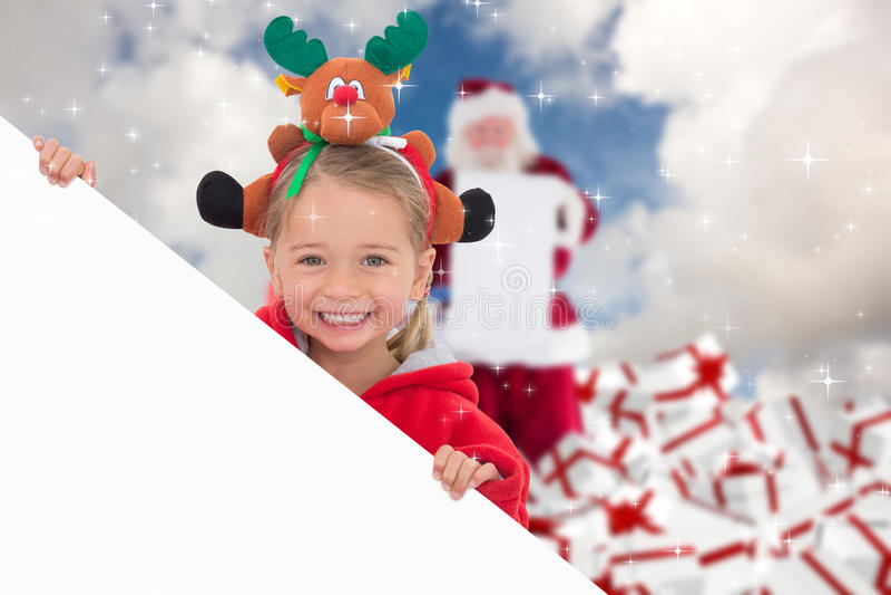 Σύνθετη εικόνα του εορταστικού μικρού κοριτσιού που παρουσιάζει αφίσα στοκ φωτογραφίες με δικαίωμα ελεύθερης χρήσης