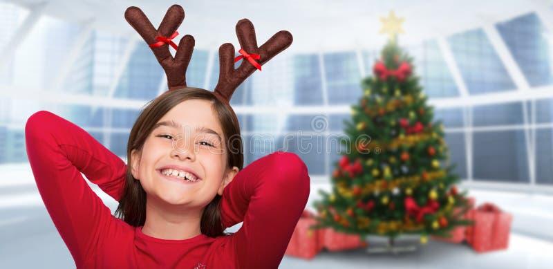 Σύνθετη εικόνα του εορταστικού μικρού κοριτσιού που φορά τα ελαφόκερες στοκ φωτογραφίες με δικαίωμα ελεύθερης χρήσης