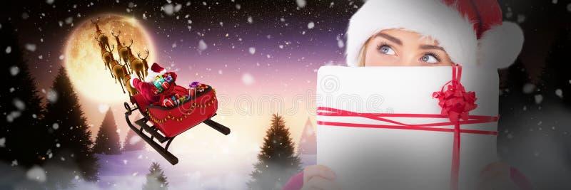 Σύνθετη εικόνα του εορταστικού ξανθού δώρου Χριστουγέννων εκμετάλλευσης στοκ φωτογραφία με δικαίωμα ελεύθερης χρήσης