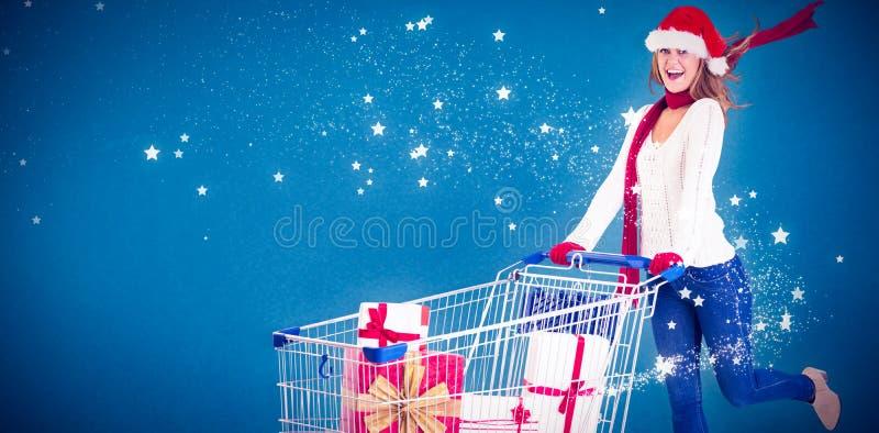 Σύνθετη εικόνα του εορταστικού ξανθού συνόλου καροτσακιών ώθησης των δώρων στοκ φωτογραφία