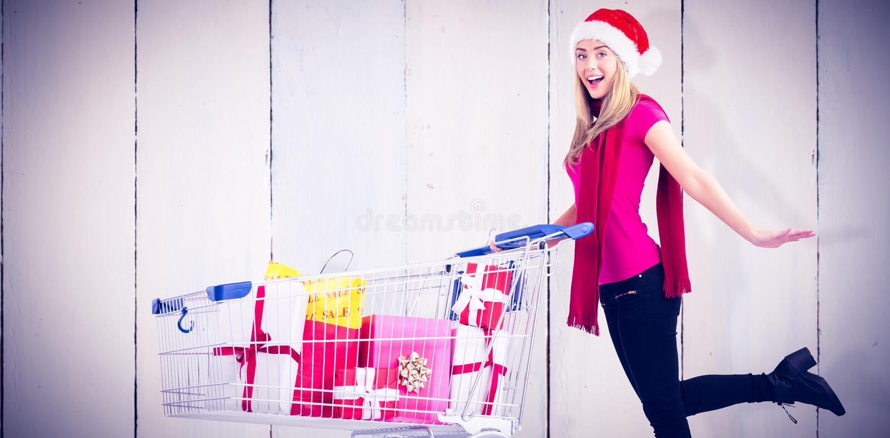 Σύνθετη εικόνα του εορταστικού ξανθού συνόλου καροτσακιών ώθησης των δώρων στοκ εικόνα με δικαίωμα ελεύθερης χρήσης