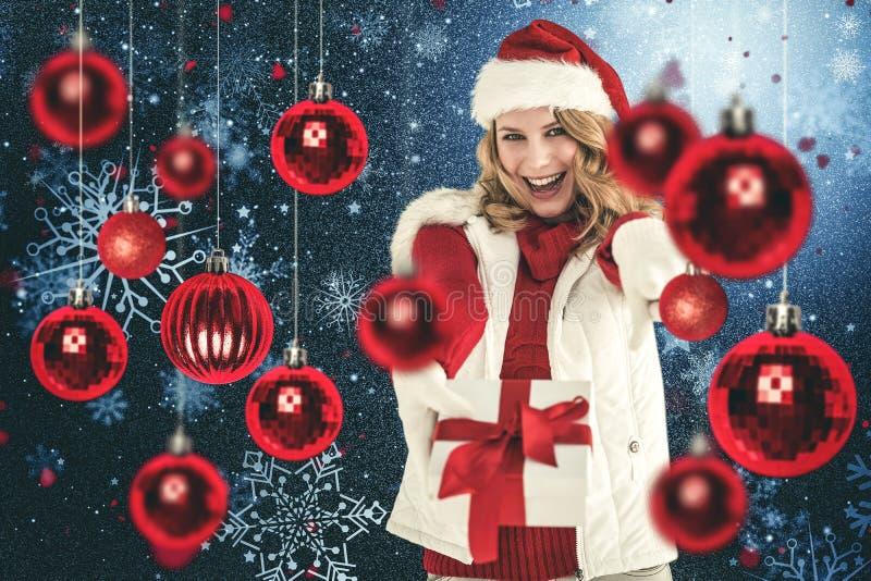 Σύνθετη εικόνα του εορταστικού ξανθού δώρου και της υπόδειξης Χριστουγέννων εκμετάλλευσης του δάχτυλού της στοκ φωτογραφία