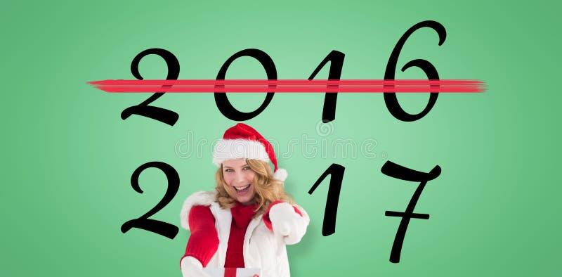 Σύνθετη εικόνα του εορταστικού ξανθού δώρου και της υπόδειξης Χριστουγέννων εκμετάλλευσης του δάχτυλού της στοκ εικόνες με δικαίωμα ελεύθερης χρήσης